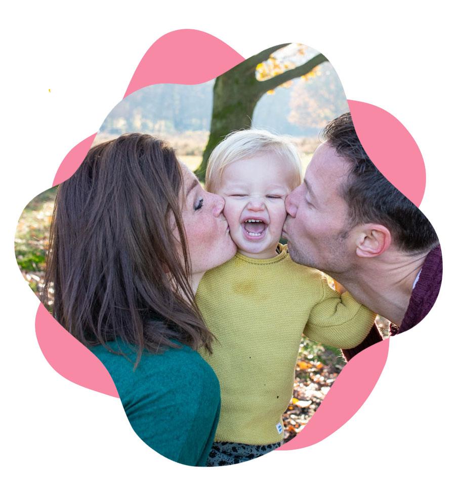 familie gezinsfoto, kind wordt gezoend door pa en ma tegelijk